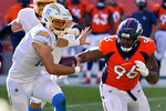 FILE - Los Angeles Chargers quarterback Justin Herbert (10) runs as Denver Broncos defensive end Shelby Harris (96) pursues during the first half of an NFL football game in Denver, in this Sunday, Nov. 1, 2020, file photo. After missing the past four games because of COVID-19, Harris will return to the Broncos lineup Sunday evening when Denver travels to Kansas City to face the Chiefs. (AP Photo/David Zalubowski, File)