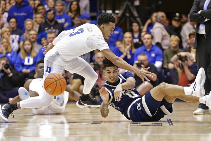 Duke's Tre Jones (3) reaches in as Georgia Tech's Michael Devoe (0) passes from the floor during the first half of an NCAA college basketball game in Durham, N.C., Saturday, Jan. 26, 2019. (AP Photo/Gerry Broome)