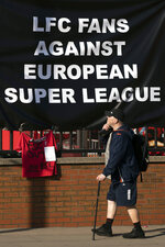 A member of the public passes a banner outside Liverpool's Anfield Stadium protesting the formation of the European Super League, Liverpool, England, Monday, April 19, 2021. Players at the 12 clubs setting up their own Super League could be banned from this year's European Championship and next year's World Cup, UEFA President Aleksander Ceferin said Monday.