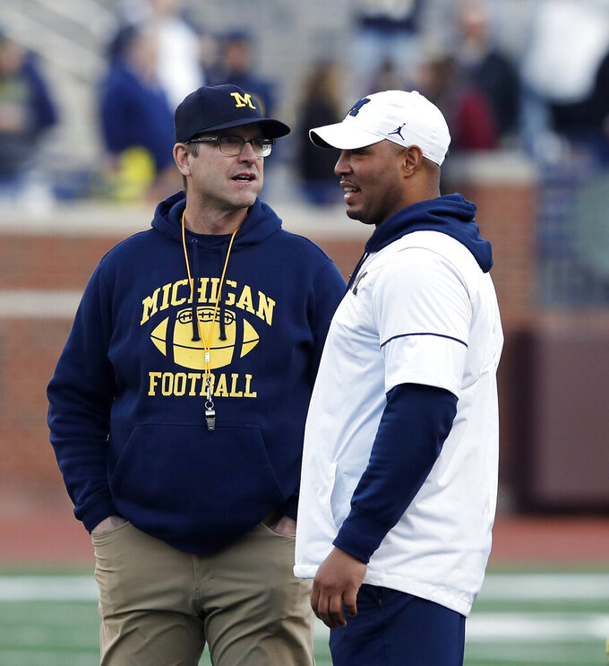 FILE-  In this April 13, 2019, file photo Michigan head coach Jim Harbaugh, left, and offensive coordinator Josh Gattis talk during the team's annual spring NCAA college football game in Ann Arbor, Mich. Harbaugh seems to be set up for success at Michigan in his fifth season, leading a program that is a popular choice to win the Big Ten. (AP Photo/Carlos Osorio, File)