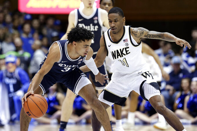 Duke guard Tre Jones (3) dribbles while Wake Forest guard Torry Johnson (11) defends during the first half of an NCAA college basketball game in Durham, N.C., Saturday, Jan. 11, 2020. (AP Photo/Gerry Broome)