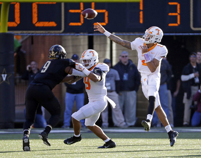 Tennessee quarterback Jarrett Guarantano (2) passes as running back Tim Jordan, center, blocks Vanderbilt linebacker Caleb Peart (9) in the first half of an NCAA college football game Saturday, Nov. 24, 2018, in Nashville, Tenn. (AP Photo/Mark Humphrey)