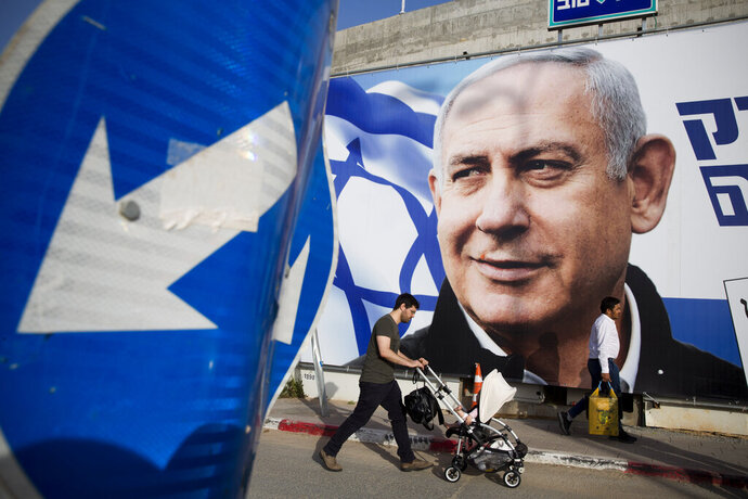FILE - In this April 7, 2019 file photo, a man walks by an election campaign billboard showing Israel's Prime Minister Benjamin Netanyahu, the Likud party leader, in Tel Aviv, Israel. As Netanyahu becomes Israel's longest-serving prime minister, he is solidifying his place as the country's greatest political survivor and the most dominant force in Israeli politics in his generation. (AP Photo/Oded Balilty, File)