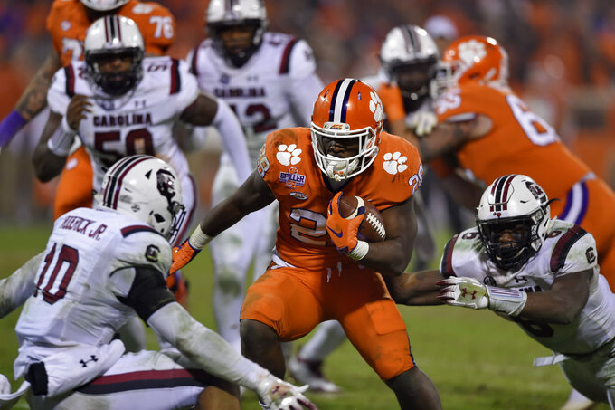 Clemson's Tavien Feaster (28) rushes for a touchdown while defended by South Carolina's R.J. , left, and D.J. Wonnum during the second half of an NCAA college football game Saturday, Nov. 24, 2018, in Clemson, S.C. Clemson won 56-35. (AP Photo/Richard Shiro)