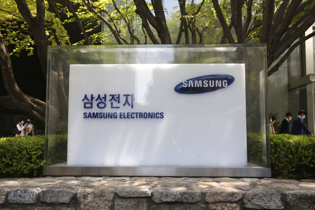 FILE - In this April 28, 2020, file photo, employees walk past a logo of the Samsung Electronics Co. at its office in Seoul, South Korea. Samsung Electronics Co. said Tuesday, July 7, its operating profit for the last quarter likely rose 23% from the same period last year. (AP Photo/Ahn Young-joon, File)