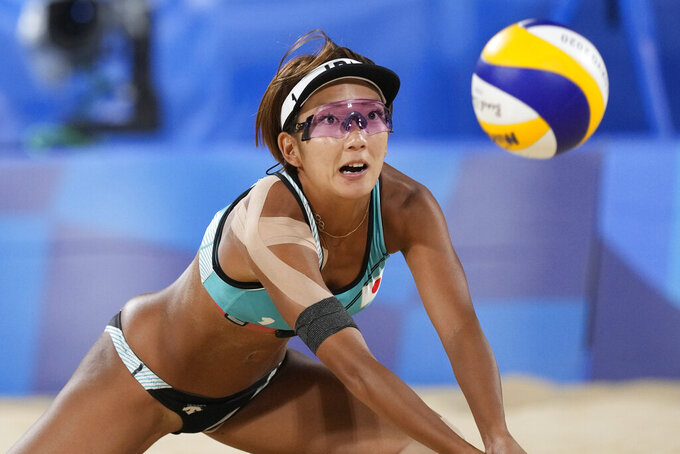 Miki Ishii, of Japan, dives for the ball during a women's beach volleyball match against Germany at the 2020 Summer Olympics, Monday, July 26, 2021, in Tokyo, Japan. (AP Photo/Petros Giannakouris)