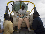 Sitting in her home's lounger, Virginia Mosvold, 84, is lowered from a truck by volunteers after being rescued from her flooded home on Ol' Freetown Farm farm in the aftermath of Hurricane Dorian before being taken to the hospital on the outskirts of Freeport, Bahamas, Wednesday, Sept. 4, 2019. Rescue crews in the Bahamas fanned out across a blasted landscape of smashed and flooded homes trying to reach drenched and stunned victims of Hurricane Dorian and take the full measure of the disaster. (AP Photo/Ramon Espinosa)