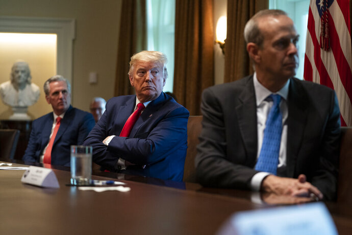 House Minority Leader Kevin McCarthy of Calif., President Donald Trump, and Chevron CEO Mike Wirth listen during a meeting with energy sector business leaders in the Cabinet Room of the White House, Friday, April 3, 2020, in Washington. (AP Photo/Evan Vucci)
