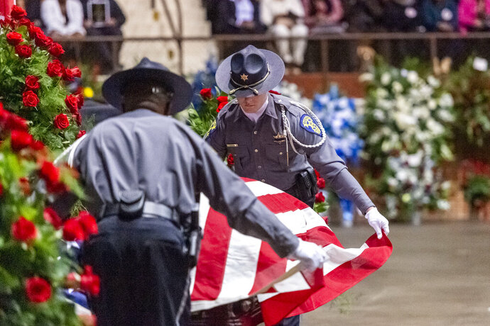 A U.S. flag is placed on the casket during the memorial service for slain Lowndes County Sheriff