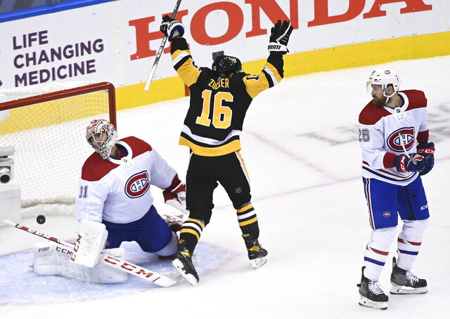 Pittsburgh Penguins left wing Jason Zucker (16) scores past Montreal Canadiens goaltender Carey Price (31) as Canadiens defenseman Jeff Petry (26) look on during the third period of an NHL hockey playoff game  Monday, Aug. 3, 2020 in Toronto. (Nathan Denette/The Canadian Press via AP)
