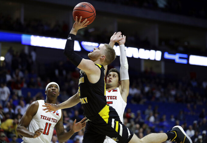 Northern Kentucky's Tyler Sharpe, center, heads to the basket past Texas Tech's Tariq Owens (11) and Davide Moretti during the first half of a first round men's college basketball game in the NCAA Tournament Friday, March 22, 2019, in Tulsa, Okla. (AP Photo/Jeff Roberson)