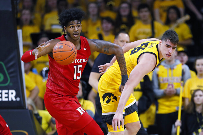 Rutgers center Myles Johnson (15) grabs a rebound in front of Iowa center Luka Garza during the first half of an NCAA college basketball game, Wednesday, Jan. 22, 2020, in Iowa City, Iowa. (AP Photo/Charlie Neibergall)