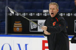 "Calgary Flames associate coach Geoff Ward gives instruction during an NHL hockey practice Tuesday, Nov. 26, 2019, in Buffalo, N.Y. Flames general manager Brad Treliving says coach Bill Peters remains on the staff but wasn't certain whether he'd be behind the bench for the next game. The team and the NHL are both investigating an allegation the Peters directed racial slurs at a player 10 years ago when the two were in the minors. Akim Aliu, a Nigerian-born player, says Peters ""dropped the N bomb several times"" in a dressing room during his rookie year. (AP Photo/Jeffrey T. Barnes)"