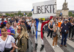 Anti-vaccine protester dressed in the colors of the French national flag holds a placard that reads liberty during a rally in Paris, Saturday, July 17, 2021. Tens of thousands of people protested across France on Saturday against the government's latest measures to curb rising COVID-19 infections and drive up vaccinations in the country. (AP Photo/Michel Euler)