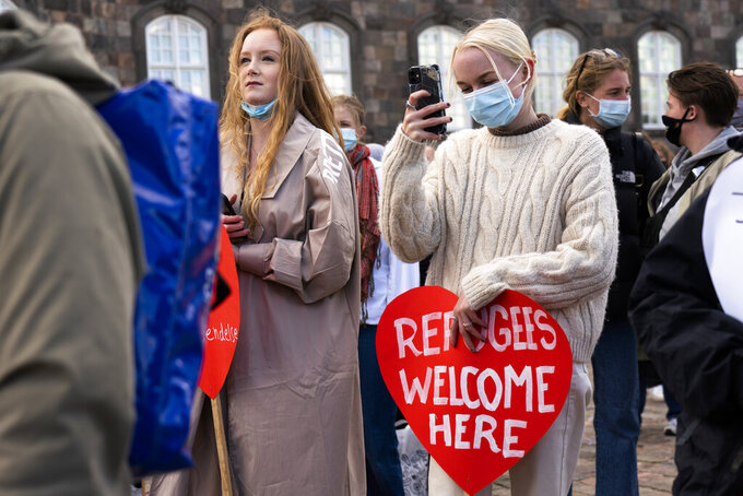People attend a demonstration against the tightening of Denmark's migration policy and the deportation orders in Copenhagen, Denmark, Wednesday, April 21, 2021. Ten years after the start of the Syrian civil war, Denmark has become the first European country to start revoking the residency permits of some refugees from the Damascus area. (AP Photo/David Keyton)