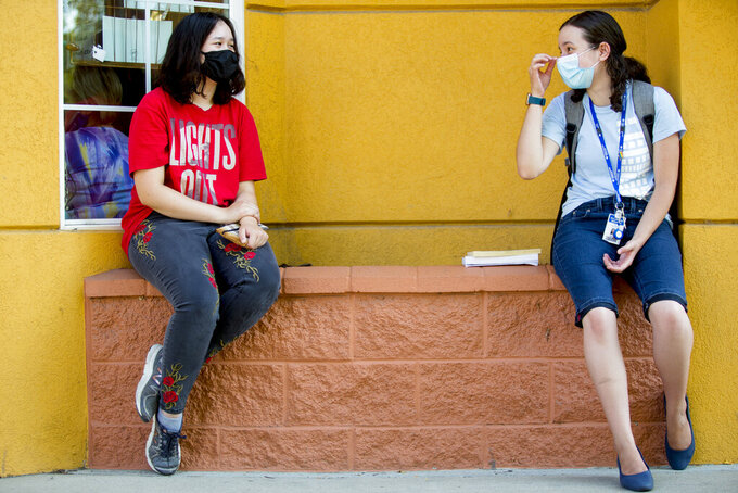 Aurora Golden-Appleton adjusts her face mask as she chats with Rylin Green, both of Provo, as they sit outside Joe Vera's Mexican Restaurant in downtown Provo, Utah, on Thursday, Aug. 27, 2020. (Isaac Hale/The Daily Herald via AP)