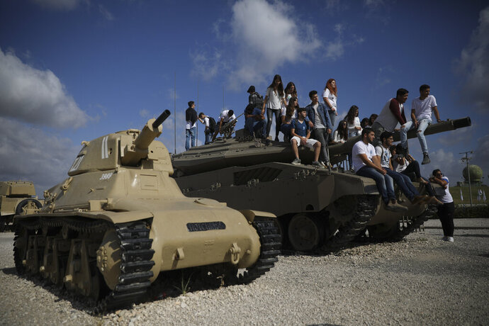 Students sit on a tank just before a ceremony marking the annual Memorial Day to remember fallen soldiers and victims of terror, at the Armored Corps memorial site in Latrun, Israel, Wednesday, May 8, 2019. (AP Photo/Oded Balilty)