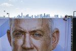 A worker hangs a massive election campaign billboard that shows the Blue and White party leader Benny Gantz, in Tel Aviv, Israel, Monday, Sept. 9, 2019. (AP Photo/Oded Balilty, File)