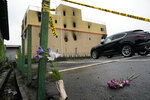 Flowers are placed near the Kyoto Animation Studio building destroyed in an arson attack Friday, July 19, 2019, in Kyoto, Japan. A man screaming