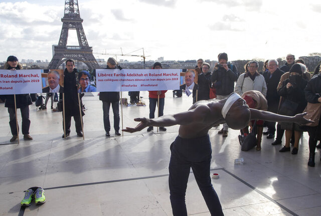 FILE - In this Feb. 11, 2020, file photo, Senegalese dancer Alioune Diagne performs during a gathering at Trocadero square in Paris, calling for the release of French scientists Fariba Adelkhah and Roland Marchal imprisoned in Iran. An Iranian court has sentenced a French-Iranian researcher to a total of six years in prison on security charges, her lawyer said Saturday, May 16, 2020. (AP Photo/Michel Euler, File)