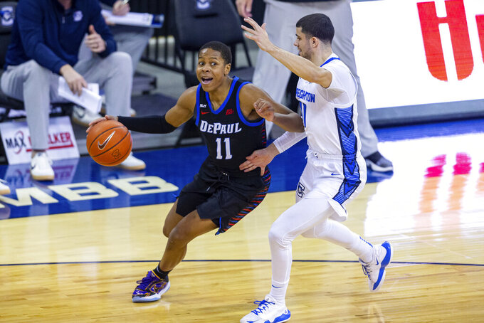 File-This Feb. 24, 2021, file photo shows DePaul guard Charlie Moore (11) driving to the basket against Creighton guard Marcus Zegarowski (11) in the first half during an NCAA college basketball game in Omaha, Neb. Moore is transferring from DePaul to Miami, his fourth school, for his final year of eligibility. Moore provides a much-needed reinforcement for the Hurricanes, who since the end of the season have lost three players via the NCAA's new transfer rule. The 5-foot-11 Moore averaged 15.5 points and 6.1 assists in 32 games for DePaul in 2019-20, and 14.4 points and 4.2 assists in 16 games this past season. He started 34 games as a freshman at California and played as a reserve for Kansas in 2018-19. (AP Photo/John Peterson, File)