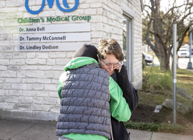 Laura Atkins, left, consoles her sister, Lisa Parker, outside the Children's Medical Group, Wednesday Jan. 27, 2021. A reported hostage situation at the Texas doctor's office ended with two people dead, authorities said. Parker's 4-year-old son was a patient of the doctor who was murdered. (Jay Janner/Austin American-Statesman via AP)