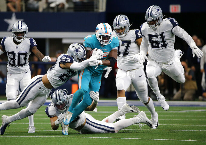 Dallas Cowboys' Darian Thompson (23) and Leighton Vander Esch, bottom, combine to stop Miami Dolphins running back Kenyan Drake (32) from gaining extra yardage in the first half of an NFL football game as Anthony Brown (30) and Kerry Hyder (51) look on in Arlington, Texas, Sunday, Sept. 22, 2019. (AP Photo/Michael Ainsworth)