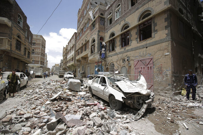 People inspect the site of an airstrike by Saudi-led coalition in Sanaa, Yemen, Thursday, May, 16, 2019. Yemen's human rights minister says heavy fighting is underway in the country's south as rebel Houthis push to gain more territory from government forces and their allies. The clashes come as the Saudi-led coalition carried out airstrikes on the capital, Sanaa, earlier on Thursday, targeting the Houthis and killing at least three civilians. (AP Photo/Hani Mohammed)