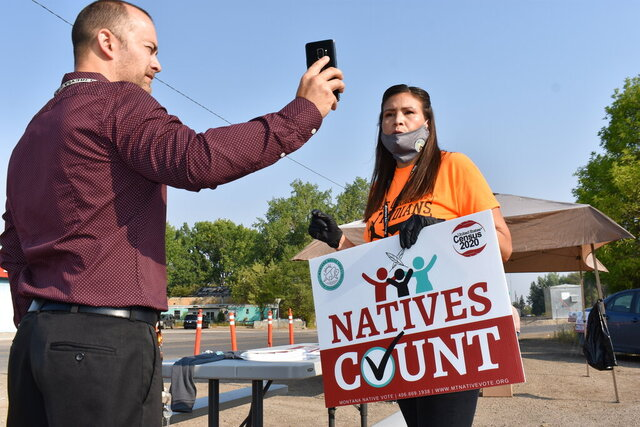 Activist Lauri Dawn Kindness, right, speaks at the Crow Indian Reservation, in Lodge Grass, Mont. on Wednesday, Aug. 26, 2020, as Lodge Grass Mayor Quincy Dabney records her for a social media campaign to increase Native American participation in the U.S. census. Kindness and other activists with Western Native Voice are trying to prevent an undercount of the tribe that could result in less federal funding. (AP Photo/Matthew Brown)