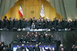 Wearing the uniform of the Iranian Revolutionary Guard, lawmakers chant slogans during an open session of parliament in Tehran, Iran, Tuesday, April 9, 2019. Chanting