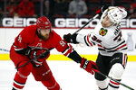 Chicago Blackhawks' Brandon Hagel (38) tangles with Carolina Hurricanes' Jani Hakanpaa (58) during the second period of an NHL hockey game in Raleigh, N.C., Tuesday, May 4, 2021. (AP Photo/Karl B DeBlaker)