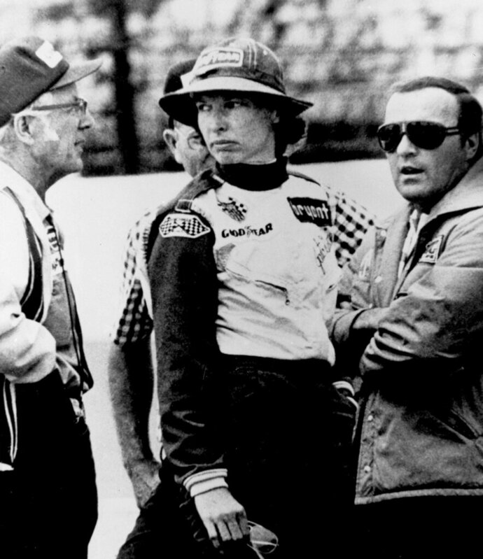 FILE - In this May 23, 1976, file photo, Janet Guthrie talks to racing car owner-builder Rolla Vollstedt, left, and A.J. Foyt, right, in the pits of the Indianapolis Motor Speedway, in Indianapolis. There was no warm reception for Janet Guthrie when she arrived at Indianapolis Motor Speedway 43 years ago. She wanted a spot in the biggest race in the world and her competitors didn't want her anywhere near the Indianapolis 500. (AP Photo/File)