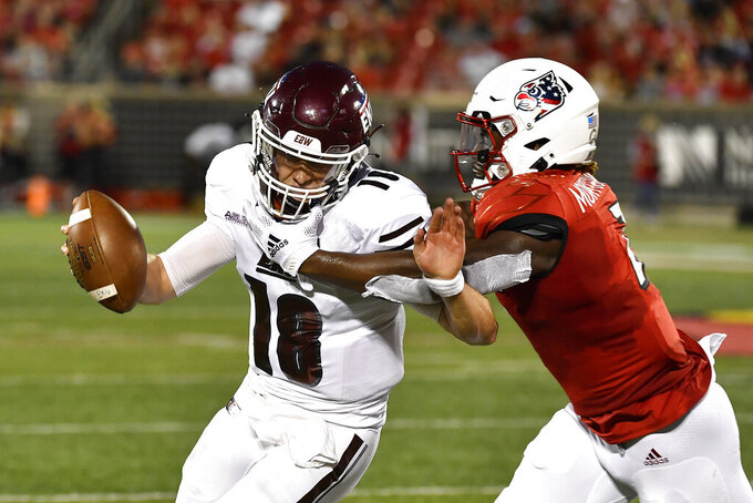Eastern Kentucky quarterback Parker McKinney (18) is grabbed by Louisville linebacker Monty Montgomery (7) during the first half of an NCAA college football game in Louisville, Ky., Saturday, Sept. 11, 2021. (AP Photo/Timothy D. Easley)