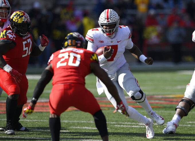 Ohio State quarterback Dwayne Haskins Jr. (7) runs with the ball against Maryland defensive back Antwaine Richardson (20) and defensive lineman Oluwaseun Oluwatimi (52) during the first half of an NCAA football game, Saturday, Nov. 17, 2018, in College Park, Md. (AP Photo/Nick Wass)