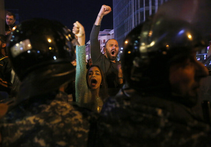 Anti-government protesters shout slogans during ongoing protests against the Lebanese political class and the financial crisis, in Beirut, Lebanon, Wednesday, Dec. 4, 2019. More than a month after the government resigned, President Michel Aoun announced on Wednesday that he will hold formal consultation to name a new prime minister next week. But protesters have already began rallying against the potential candidate for the job, saying he is too close to the political elite they have been calling on to step down. (AP Photo/Hussein Malla)