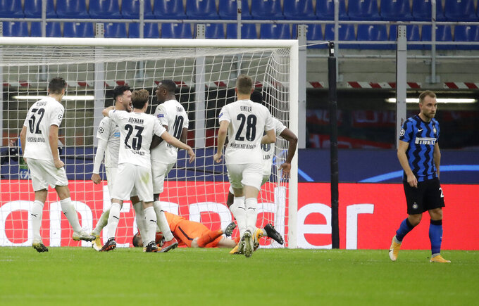Moenchengladbach's Ramy Bensebaini, second from left, celebrates with his teammates after scoring his side's opening goal during the Champions League group B soccer match between Inter Milan and Borussia Moenchangladbach at the San Siro stadium in Milan, Italy, Wednesday, Oct. 21, 2020. (AP Photo/Luca Bruno)