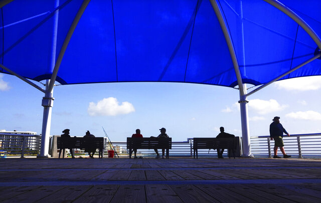 People enjoy the view at the Fisher Family Pompano Beach Pier, Wednesday, Sept. 2, 2020, in Popano Beach, Fla. Broward County beaches will remain open for the upcoming Labor Day weekend holiday. (Joe Cavaretta/South Florida Sun-Sentinel via AP)