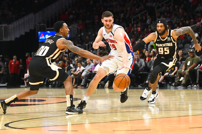Detroit Pistons guard Sviatoslav Mykhailiuk, center, tries to split the defense of Atlanta Hawks guards Jeff Teague (00) and DeAndre' Bembry (95) during the second half of an NBA basketball game Saturday, Jan. 18, 2020, in Atlanta. (AP Photo/John Amis)