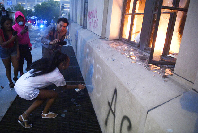 RETRANSMISSION TO INDICATE THAT IT WAS AFTER THE RALLY - A protester spray paints on the outside of the Metro Courthouse in Nashville, Tenn., Saturday, May 30, 2020, after a demonstration over the death of George Floyd. Protests were held throughout the country over the death of Floyd, a black man who died after being restrained by Minneapolis police officers on May 25. (Andrew Nelles/The Tennessean via AP)