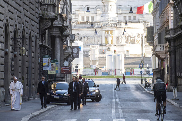 Pope Francis walks to reach S. Marcello al Corso church, where there is a miraculous crucifix that in 1552 was carried in a procession around Rome to stop the great plague, Sunday, March 15, 2020. For most people, the new coronavirus causes only mild or moderate symptoms. For some, it can cause more severe illness, especially in older adults and people with existing health problems. (Vatican News via AP)