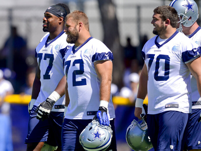 FILE - In this July 24, 2014, file photo, Dallas Cowboys offensive tackle Tyron Smith (77), center Travis Frederick (72) and guard Zack Martin (70) take the field for afternoon practice during an NFL football training camp in Oxnard, Calif. The Cowboys invested heavily in their offensive line and have become consistent winners behind the unit with the NFL's highest salary-cap figure. While Dallas isn't the only example of a club benefiting from a heavy investment up front, the New England Patriots are several notches higher than Dallas as an elite team with a more frugal approach. (AP Photo/Gus Ruelas, File)