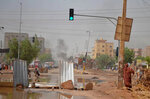 Smoke rises behind barricades laid by protesters to block a street in the Sudanese capital Khartoum to stop military vehicles from driving through the area on Wednesday, June 5, 2019. The death toll in Sudan amid a violent crackdown on pro-democracy protesters and the dispersal of their peaceful sit-in earlier this week in the capital climbed on Wednesday, protest organizers said. (Mohammed Najib via AP)