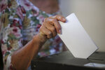 A woman casts her ballot at a polling station in Lisbon Sunday, Oct. 6, 2019. Portugal is holding a general election Sunday in which voters will choose members of the next Portuguese parliament. (AP Photo/Armando Franca)