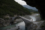 In this June 18, 2019 photo, a man crosses a bridge over the Langarica River, a tributary to the Vjosa near the city of Permet, Albania. Albania's government has set in motion plans to dam the Vjosa and its tributaries to generate much-needed electricity for one of Europe's poorest countries, with the intent to build eight dams along the main river. (AP Photo/Felipe Dana)