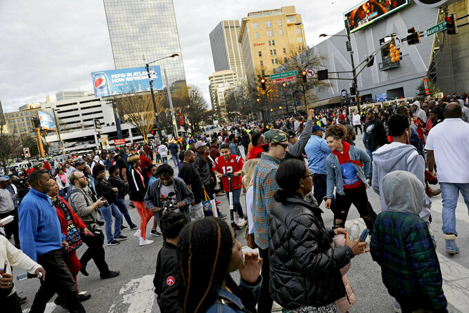 Pedestrians cross a busy intersection near Mercedes-Benz Stadium ahead of Sunday's NFL Super Bowl 53 football game between the Los Angeles Rams and New England Patriots in Atlanta, Saturday, Feb. 2, 2019. (AP Photo/David Goldman)