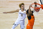Oklahoma State's Matthew-Alexander-Moncrieffe (12) gets past West Virginia's Emmitt Matthews Jr. (11) to put up a shot during the first half of an NCAA college basketball game in the second round of the Big 12 men's tournament in Kansas City, Mo., Thursday, March 11, 2021. (AP Photo/Charlie Riedel)