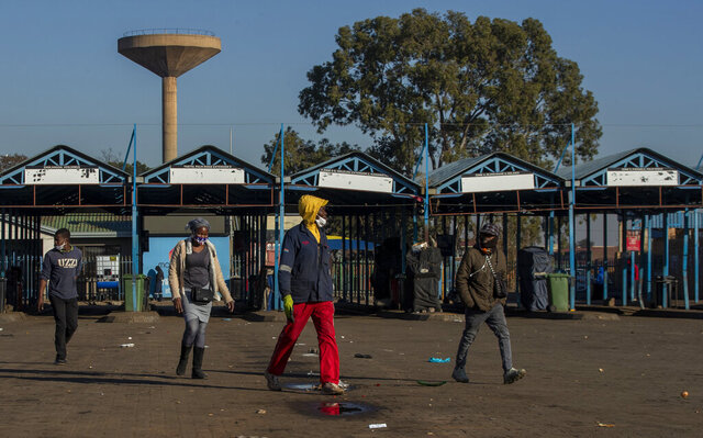 Stranded commuters walks away from a deserted taxi rank in Katlehong, South Africa, Monday, June 22, 2020, as taxi drivers affiliated to the SA National Taxi Council (Santaco) protested against what it believes to be insufficient government relief offered to the industry. South Africa's largest city, Johannesburg, has been hit by a strike by mini-bus taxis, preventing many thousands of people from getting to work on Monday, as the country reopens its economy even as cases of COVID-19 are increasing. (AP Photo/Themba Hadebe)
