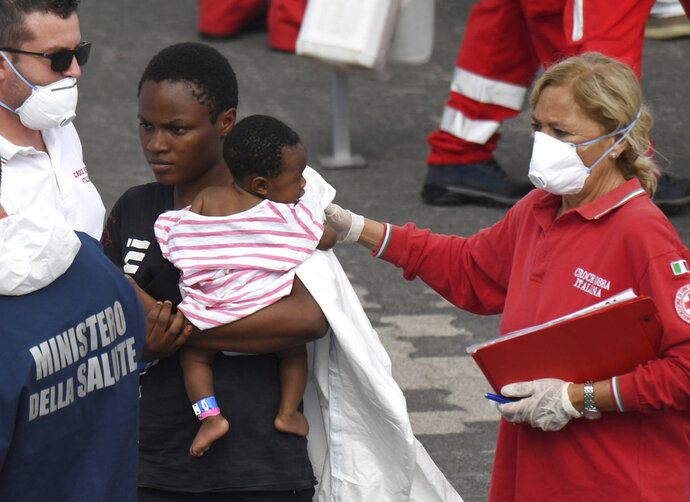 A migrant woman and baby wait for a health check up after disembarking from Italian Coast Guard vessell