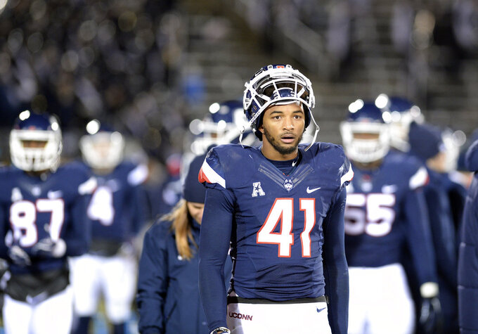 Connecticut linebacker Marshe Terry (41) and teammates leave the field at the end of an NCAA college football game against Temple Saturday, Nov. 24, 2018, in East Hartford, Conn. (AP Photo/Stephen Dunn)