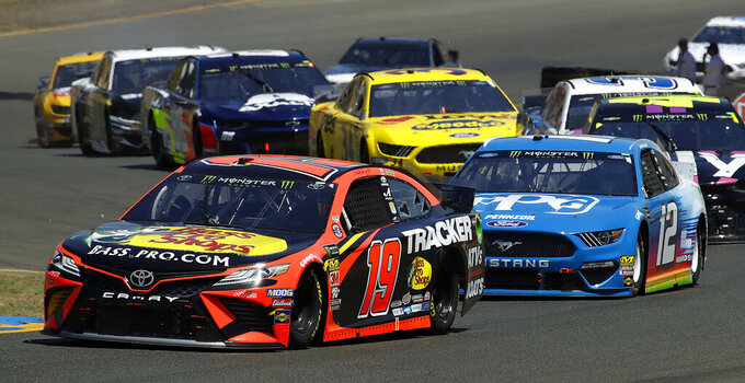 Martin Truex Jr. (19) leads the pack through a turn during a NASCAR Sprint Cup Series auto race Sunday, June 23, 2019, in Sonoma, Calif. (AP Photo/Ben Margot)